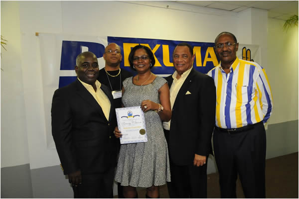 Exuma Conventions-Jen Dames receives her certificate signifying that she is a stalwart councilor of the PLP at the Exuma Mini Convention on 29th November at Ramsay, Exuma.  The photo shows from left: Deputy Prime Minister Philip Davis, Exuma MP Anthony Moss, the Prime Minister Perry Christie and the PLP Chair Bradley Roberts.  The photo is by Peter Ramsay of the Bahamas Information Services.