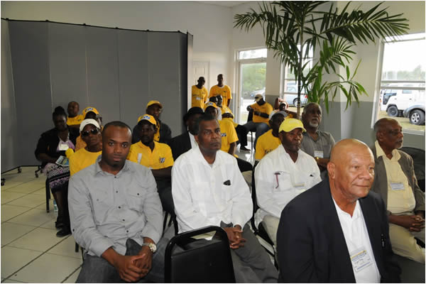 Exuma Conventions-Fred Mitchell MP for Fox Hill at centre looking on at the Exuma Mini Convention with Consul General for Atlanta Randy Rolle at the left of the picture and Danny Strachan of the Exuma Foundation in the yellow hat.  The photo was taken on 29th November at Ramsay, Exuma by Peter Ramsay of the Bahamas Information Services.